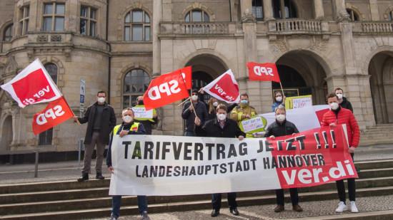 """Mehrere Personen stehen mit Fahnen und einem Transparent mit der Aufschrift """"Tarifvertrag jetzt!!! Landeshauptstadt Hannover ver.di"""" vor dem hannoverschen Rathaus"""